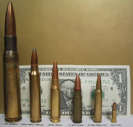 6 rifle cartridges in front of a U.S. dollar bill to compare sizes
