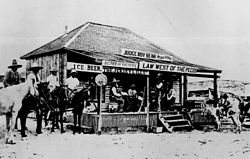 A old photograph of the Jersey Lily saloon with men on the porch and on horseback beside it