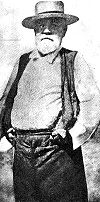 A man with a grey bear in a white shirt, vest, and dark trowsers