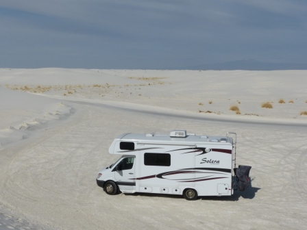 Our white motorhome parked on a flat gypsum bed with white dunes in the distance