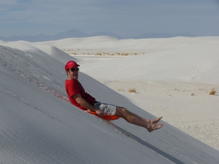 Patrick in red shirt and hats and beige shorts sliding on a plastic disk down a white sand dune