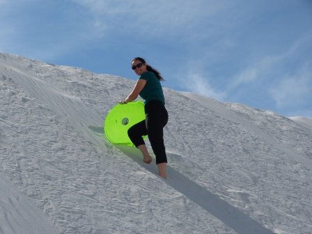 Diane walking up a white sand dune with a green plastic disc