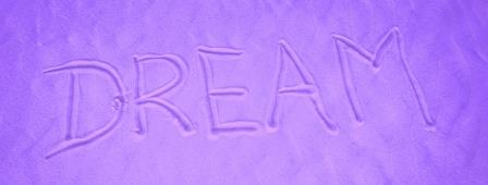 The word 'DREAM' written in sand with a puple tinge