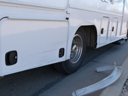 A view along the right side of our motorhome showing damage with a fender on the ground