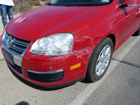 A red Volkswagen Jetta with  with body damage to the front left corner and the legs of the other driver