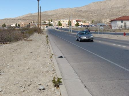 A view down the street showing a car approaching in the rightmost lane and the paved shoulder beside the curb