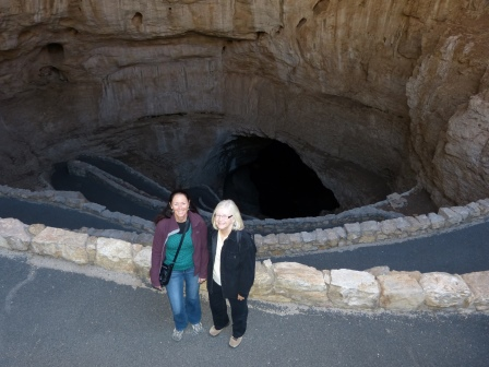 Diane and Beth standing on a paved path with many swtichbacked paths visible extending into the darkness below them