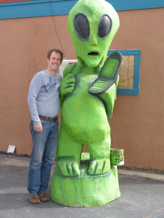 Patrick standing beside large green wood carving of an alientholding a cell phone