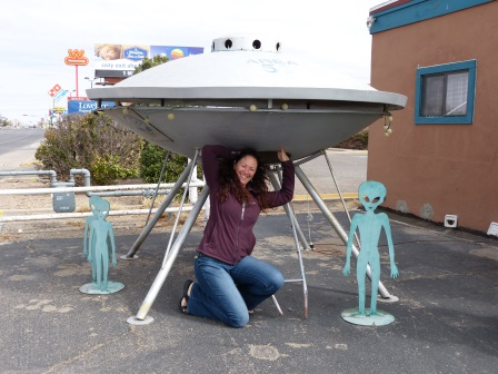 Diane croching beneath a silver model of a flying disk with little blue alien figures beside
