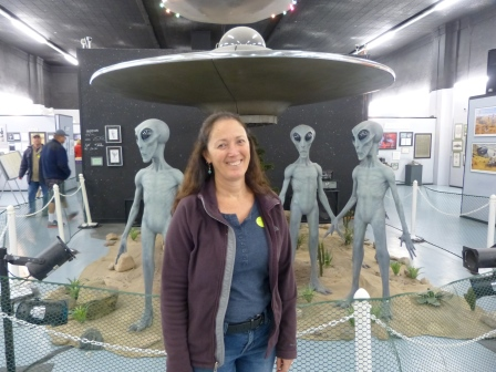 Diane standing in front of flying disc and aliens