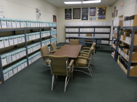 Rows of boxes containing UFO research materials around a reading table