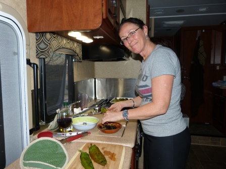 Diane cooking in the small galley kitchen of our motorhome with roasted green chilies on the counter