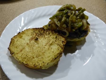 Toasted bun with a hamburger piled higher with strips of green chili on a wite dinner plate