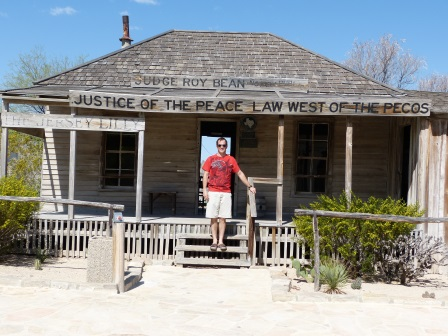 "Patrick standing in front of a small wooden building with sign, The Jersey Lily"" and ""Law West of the Pecos"""