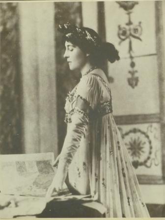 A woman in profile wearning a long white dress