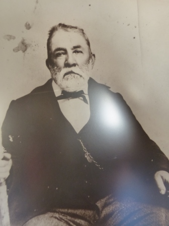 Roy Bean in black suit, white shirt, and bow tie