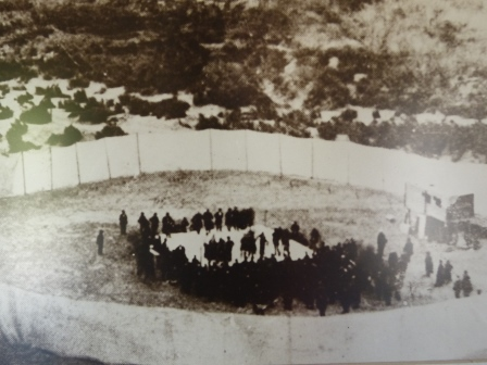 An old photo of a white fabric ring around a smaller ring of specatators watching a boxing match on the sand
