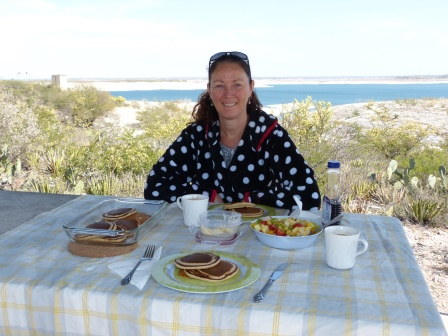 Diane seated at a picnic table with pancakes and gruit ready to eat with a lake in the background