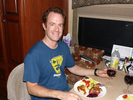 Patrick seated at the table with a roast turkey dinner on the plate in front of him and a glass of wine