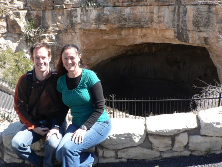 Patrick and Diane seated on a stone wall with the large, dark cave mouth behind us